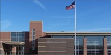 Image of Hebron High School's front entrance with the American Flag in the foreground