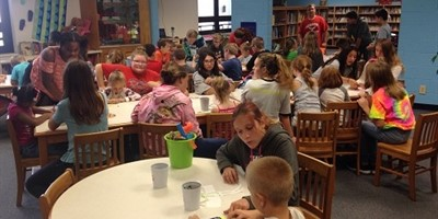 Elementary and Middle School Students working together in the Library.
