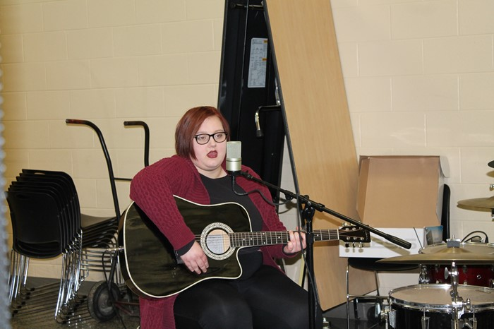 Student playing guitar and singing at Empty Bowls 2017