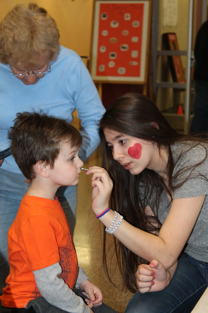 Student face painting young boy at Empty Bowls 2017
